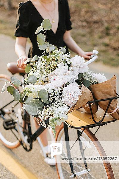 Junge Frau schiebt Fahrrad mit Blumenstrauss auf der Landstrasse  Hals nach unten  Menemsha  Martha's Vineyard  Massachusetts  USA