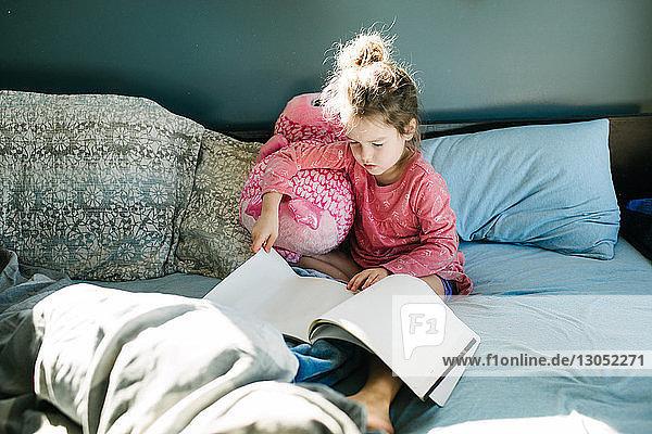 Kleines Mädchen liest im Bett