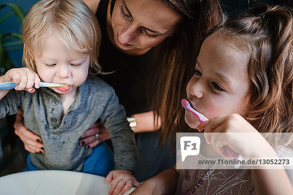 Mutter hilft Kindern beim Zähneputzen