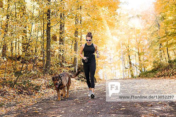 Frau joggt mit Hund im Wald