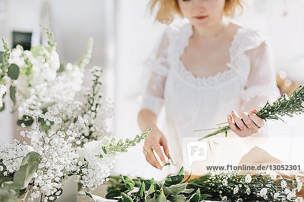 Junge Frau in weißem Kleid  weiße Blumen arrangierend  Mittelteil