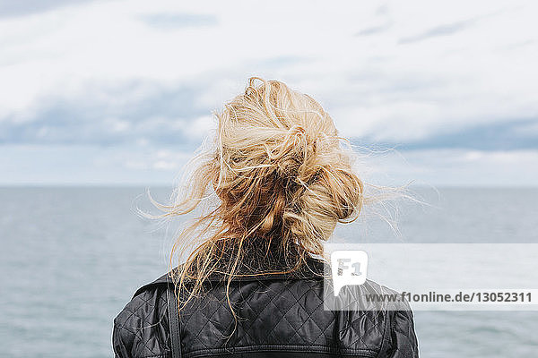 Young woman looking out to sea  rear view  Menemsha  Martha's Vineyard  Massachusetts  USA