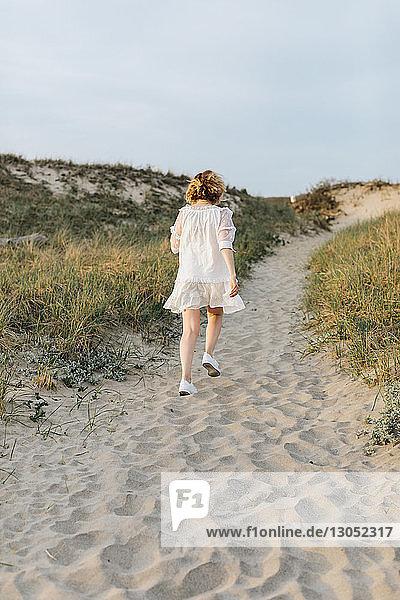 Junge Frau in weissem Kleid beim Spaziergang über die Küstendünen  Rückansicht  Menemsha  Martha's Vineyard  Massachusetts  USA