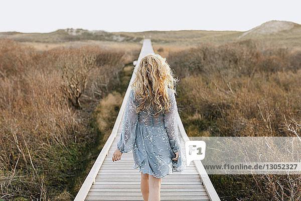 Young woman strolling on coastal dune boardwalk  rear view  Menemsha  Martha's Vineyard  Massachusetts  USA