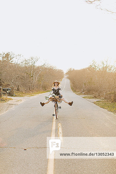 Young woman riding bicycle with legs raised on rural road  Menemsha  Martha's Vineyard  Massachusetts  USA