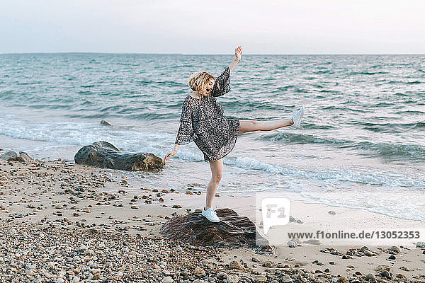 Junge Frau balanciert auf Strandfelsen  Menemsha  Martha's Vineyard  Massachusetts  USA