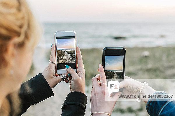 Zwei junge Frauen fotografieren den Strand mit Smartphones,  über die Schulter gesehen,  Menemsha,  Martha's Vineyard,  Massachusetts,  USA