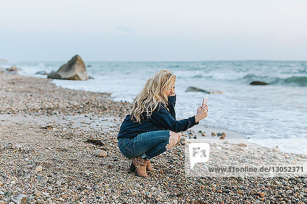 Junge Frau kauert am Strand und schaut auf ihr Smartphone  Menemsha  Martha's Vineyard  Massachusetts  USA