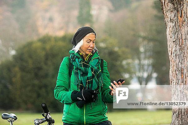Reife Frau benutzt Smartphone im Park