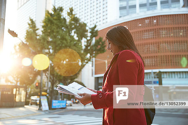 Businesswoman reading newspapers in city  Seoul  South Korea