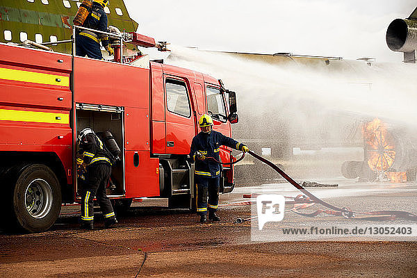 Firemen training  spraying water from fire engine at mock airplane engine