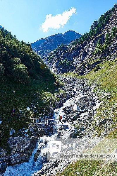 Hiker crossing narrow bridge  Mont Cervin  Matterhorn  Valais  Switzerland