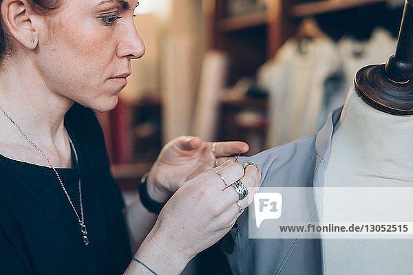 Modedesigner heftet Kleidungsstück an Schnullerpuppe der Schneiderin Modedesigner heftet Kleidungsstück an Schnullerpuppe der Schneiderin