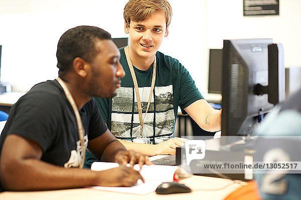 Männliche Hochschulstudenten arbeiten am Computer im College-Klassenzimmer