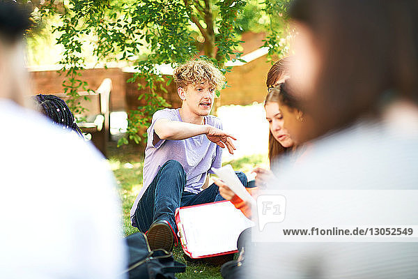 Männliche und weibliche Hochschulstudenten diskutieren über Papierkram auf dem Rasen des College-Campus  Blick über die Schulter