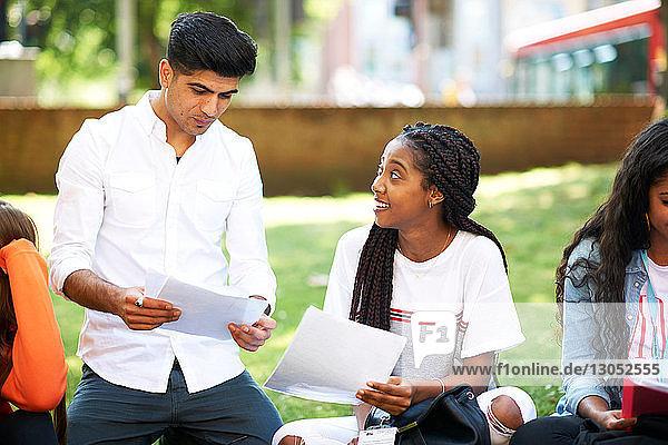 Weibliche und männliche Hochschulstudenten diskutieren über Papierkram auf dem Rasen des College-Campus