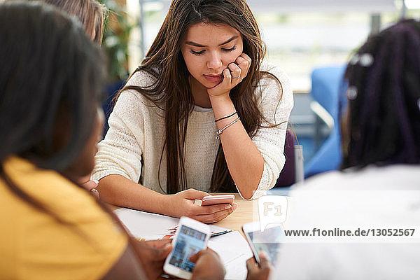 Hochschulstudentinnen  die im College-Klassenzimmer auf Smartphones schauen