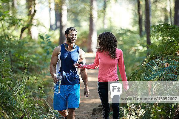 Männliche und weibliche Läufer teilen sich Flaschenwasser im Wald