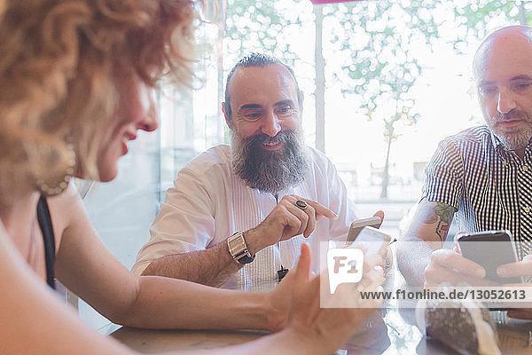 Mittelgroße erwachsene Frau und männliche Freunde schauen sich im Café Smartphones an