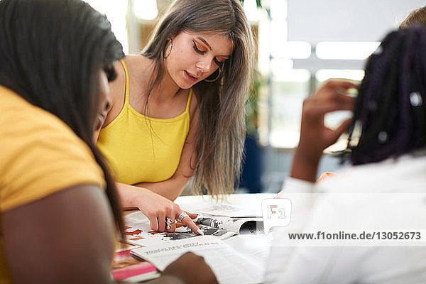 Weibliche Hochschulstudentinnen,  die im Hochschulunterricht an einem Projekt arbeiten