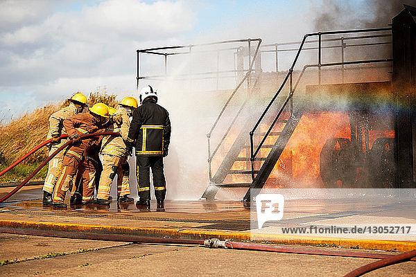 Firemen training  firemen spraying water at training facility stairway