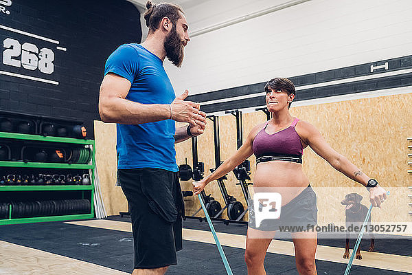 Trainer guiding pregnant woman using ropes in gym