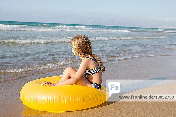 Mädchen sitzt auf einem gelben Schlauchboot am Strand  Castellammare del Golfo  Sizilien  Italien