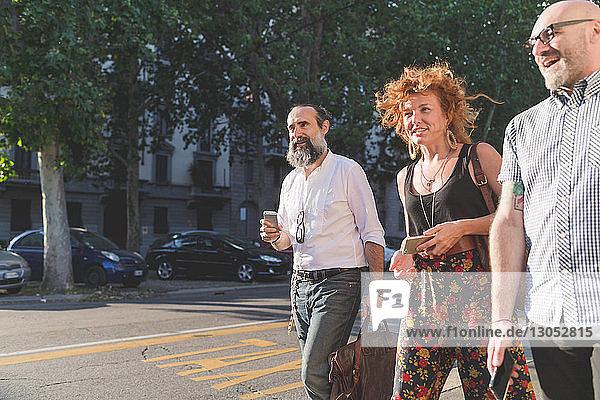 Mittelgroße erwachsene Frau und männliche Freunde unterhalten sich beim Spaziergang auf dem Bürgersteig der Stadt