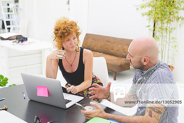 Businessman and woman having meeting and discussion at office desk