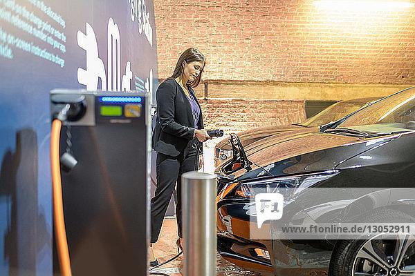 Geschäftsfrau,  die ihr Auto an einer Ladestation für Elektrofahrzeuge anschließt,  Manchester,  UK