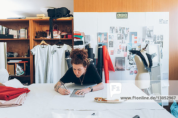 Fashion designer drawing and creating dressmaker's pattern