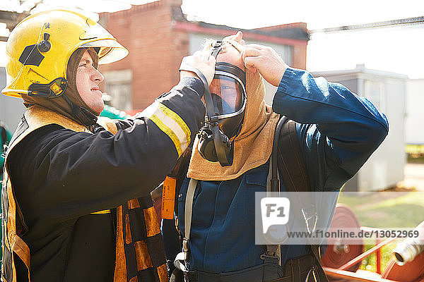 Firemen training  supervisor helping fireman with breathing apparatus at training facility
