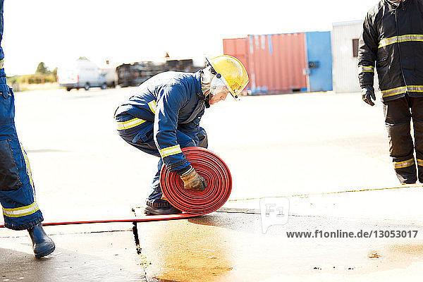 Firemen training  fireman unrolling fire hose at training facility