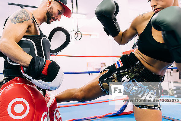 Male and female boxers working out in boxing ring