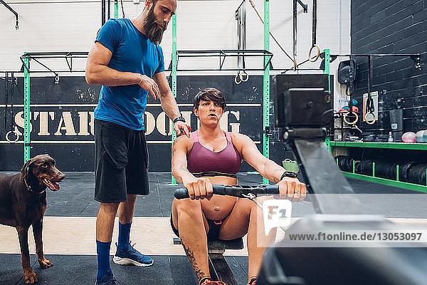 Trainerin führt schwangere Frau auf Rudergerät im Fitnessstudio