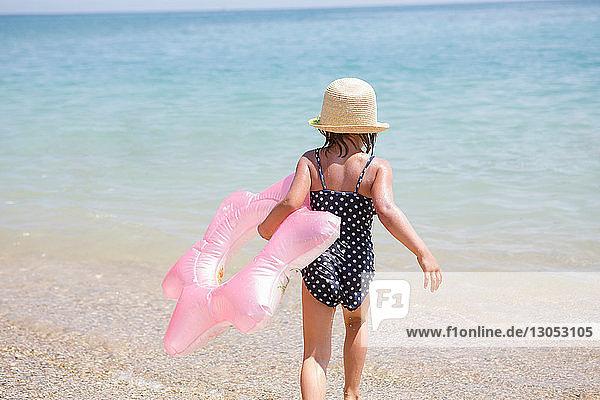 Mädchen trägt rosa Schlauchboot ins Meer  Scopello  Sizilien  Italien