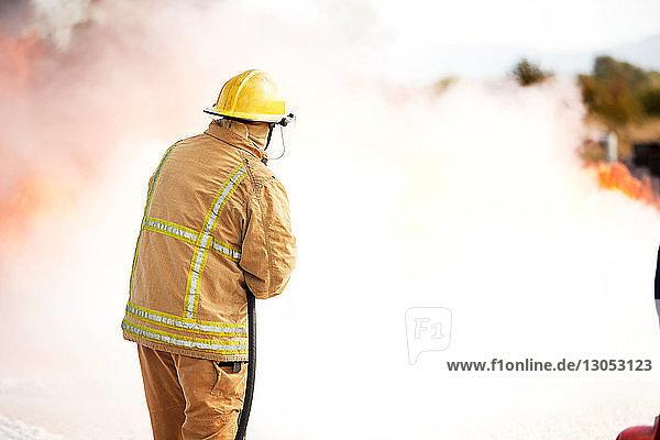 Firemen training  fireman spraying firefighting foam at training facility