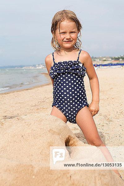Süßes Mädchen baut Sandburg am Strand in geflecktem Badeanzug  Porträt  Castellammare del Golfo  Sizilien  Italien