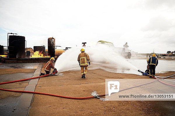 Firemen training  spraying water onto fire at training facility