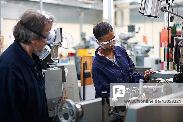Dozent  der den Studenten die Bedienung der Maschine in der Werkstatt lehrt