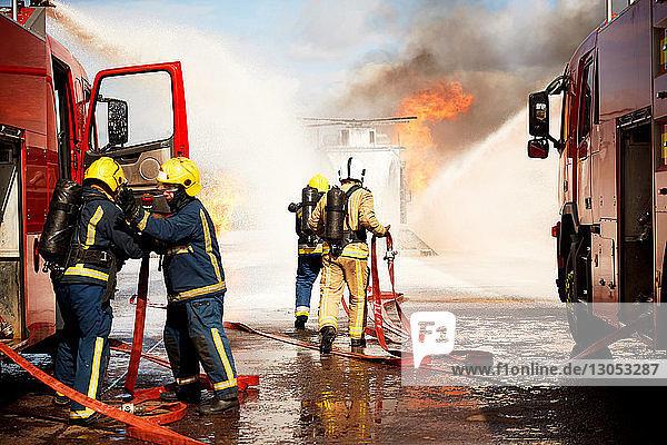 Ausbildung von Feuerwehrleuten  Team von Feuerwehrleuten löscht Scheinhubschrauberfeuer in der Ausbildungsstätte