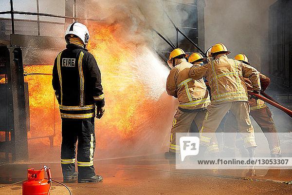 Firemen training  firemen spraying water at fire at training facility  rear view