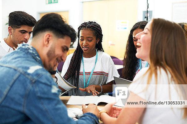 Weibliche und männliche Hochschulstudenten diskutieren Projekt im Hochschulklassenzimmer