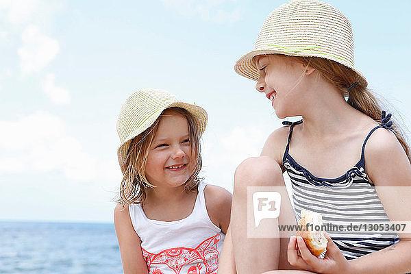 Zwei Mädchen mit Sonnenhüten essen Sandwiches am Strand  Scopello  Sizilien  Italien