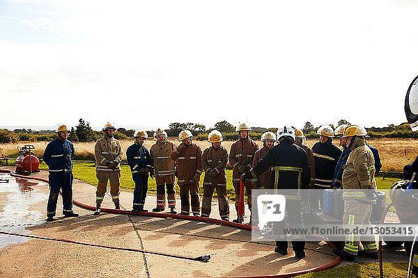 Firemen training  team of firemen listening to supervisor at training facility