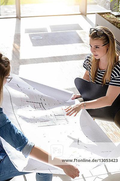 Kollegen beim Brainstorming über Diagramme im hellen Sonnenlicht