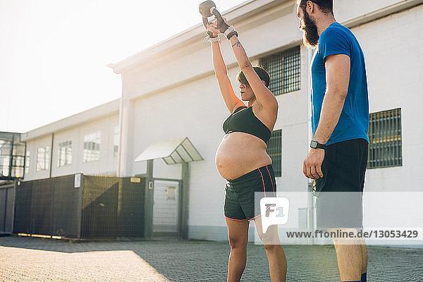 Schwangere Frau und Personal Trainerin arbeiten im Freien