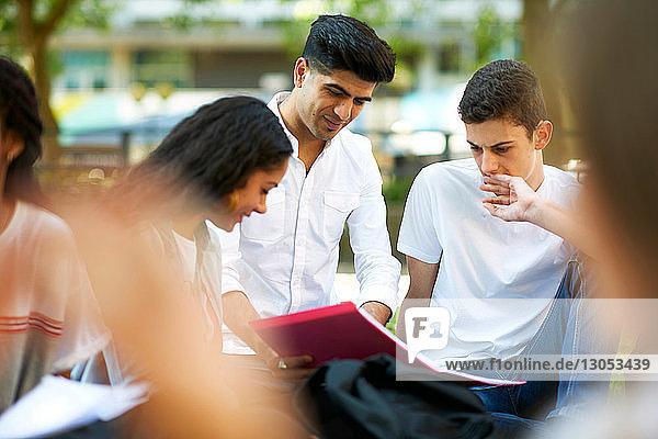 Männliche und weibliche Hochschulstudenten betrachten Papierkram auf dem Rasen des College-Campus  Blick über die Schulter