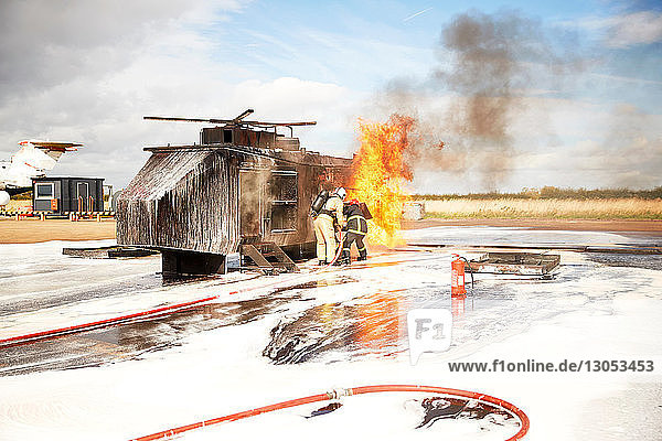 Firemen training  team of firemen spraying firefighting foam at mock helicopter fire at training facility