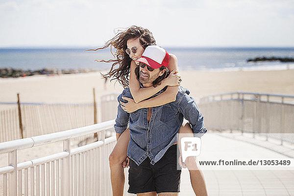 Mann nimmt Frau Huckepack  während er am Strand auf der Strandpromenade spazieren geht